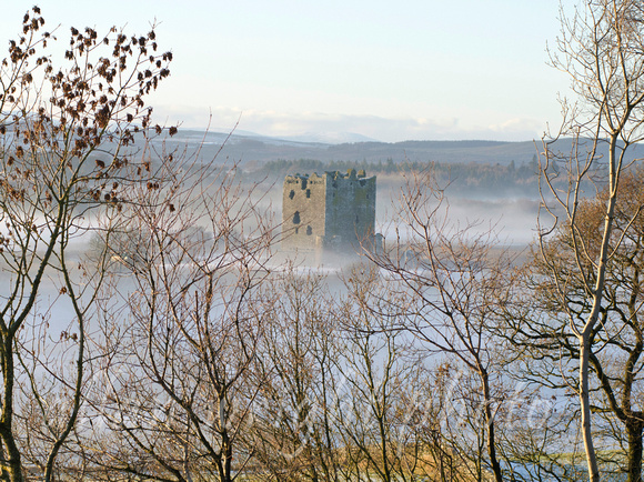 Threave Castle in winter with trees in foreground
